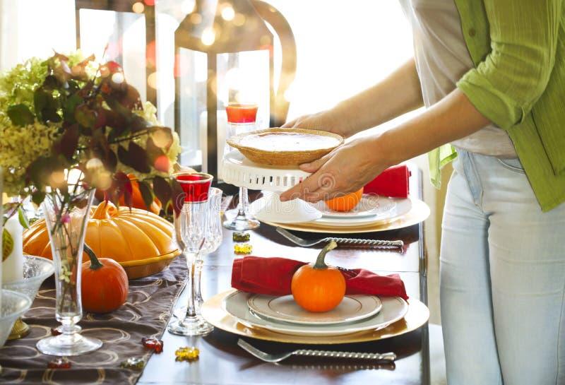 Εξυπηρετώντας πίτα κολοκύθας γυναικών στο κόμμα ημέρας των ευχαριστιών στοκ εικόνες
