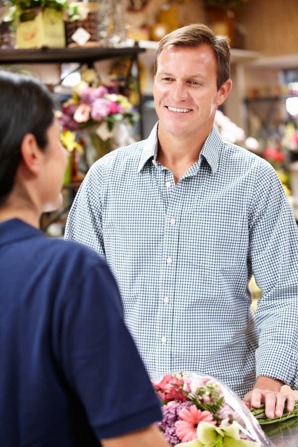 Εξυπηρετώντας πελάτης ανθοκόμων στοκ εικόνα