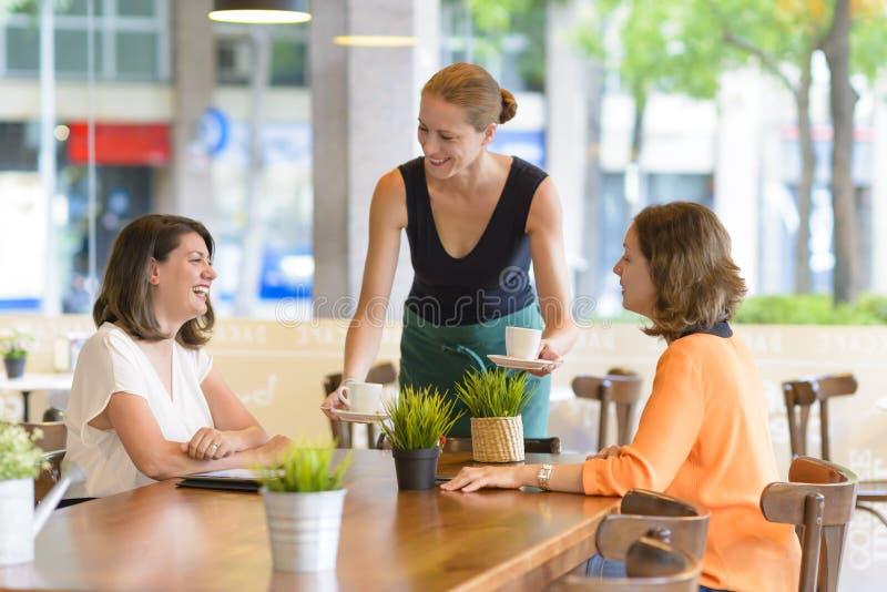 Εξυπηρετώντας πελάτες σερβιτορών στοκ φωτογραφία