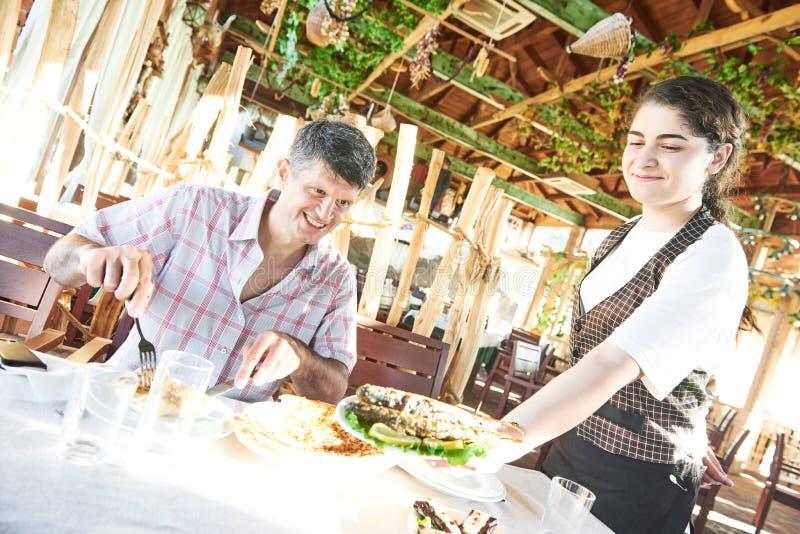 Εξυπηρετώντας τρόφιμα σερβιτορών στον πελάτη στοκ φωτογραφία με δικαίωμα ελεύθερης χρήσης