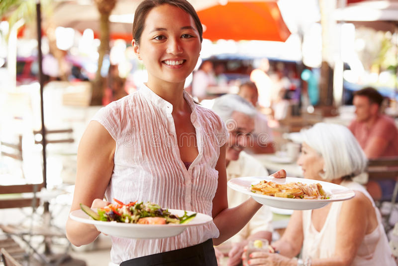 Εξυπηρετώντας τρόφιμα σερβιτορών στο υπαίθριο εστιατόριο στοκ φωτογραφία με δικαίωμα ελεύθερης χρήσης