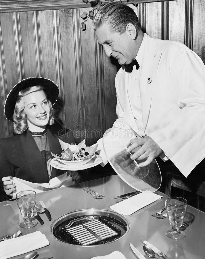 Εξυπηρετώντας τρόφιμα σερβιτόρων σε μια γυναίκα σε ένα εστιατόριο (όλα τα πρόσωπα που απεικονίζονται δεν ζουν περισσότερο και καν στοκ φωτογραφία
