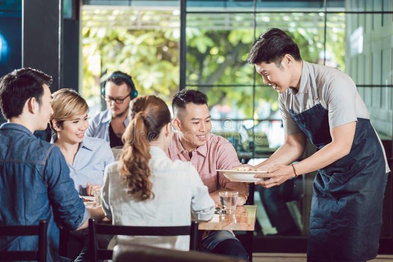 Εξυπηρετώντας τρόφιμα σερβιτόρων στο εστιατόριο στοκ φωτογραφία με δικαίωμα ελεύθερης χρήσης