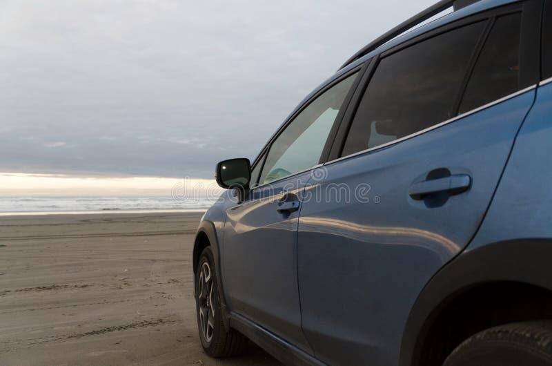 Εξωτερικές λεπτομέρειες του μπλε hatchback στην παραλία άμμου στο φως σούρουπου στοκ εικόνες