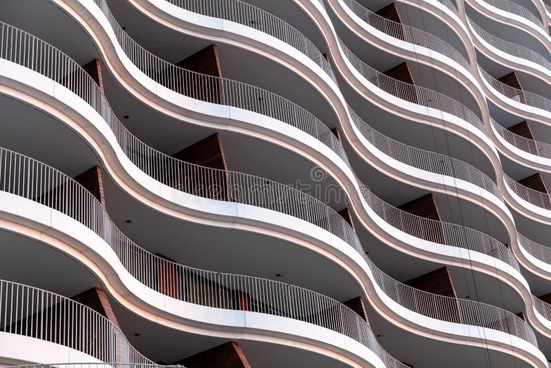 Εξωτερική άποψη προσόψεων αρχιτεκτονικής του σύγχρονου τοίχου κτιρίου γραφείων με τα φω'τα και τις σκιές στοκ εικόνα