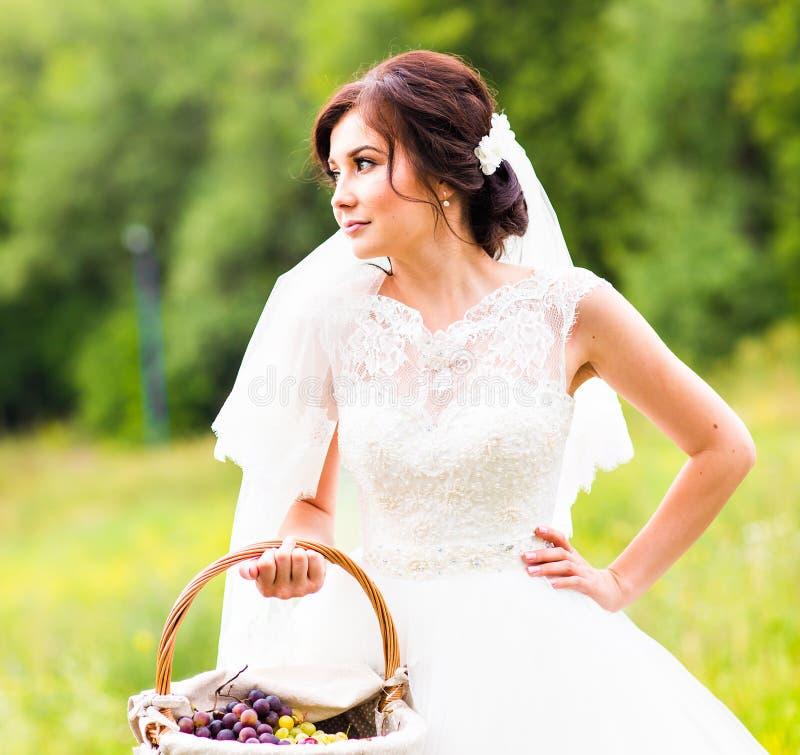 Εξωτερικό πορτρέτο της όμορφης νέας νύφης με το καλάθι σε ένα πάρκο στοκ εικόνες