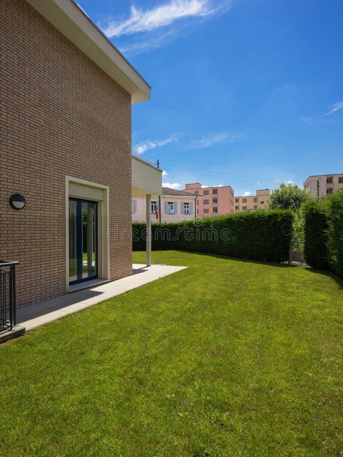 Εξωτερικό του σπιτιού με τον πράσινο κήπο κατά τη διάρκεια μιας ηλιόλουστης ημέρας στοκ φωτογραφίες