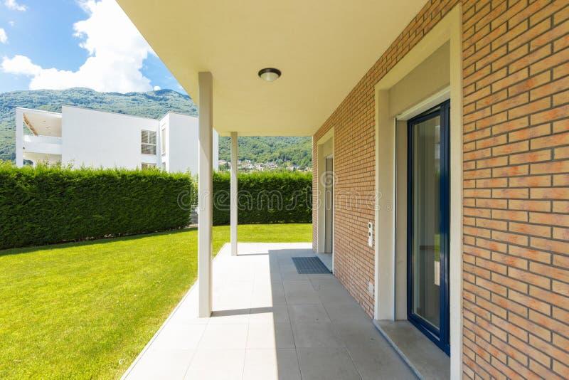 Εξωτερικό του σπιτιού με τον πράσινο κήπο κατά τη διάρκεια μιας ηλιόλουστης ημέρας στοκ εικόνες με δικαίωμα ελεύθερης χρήσης
