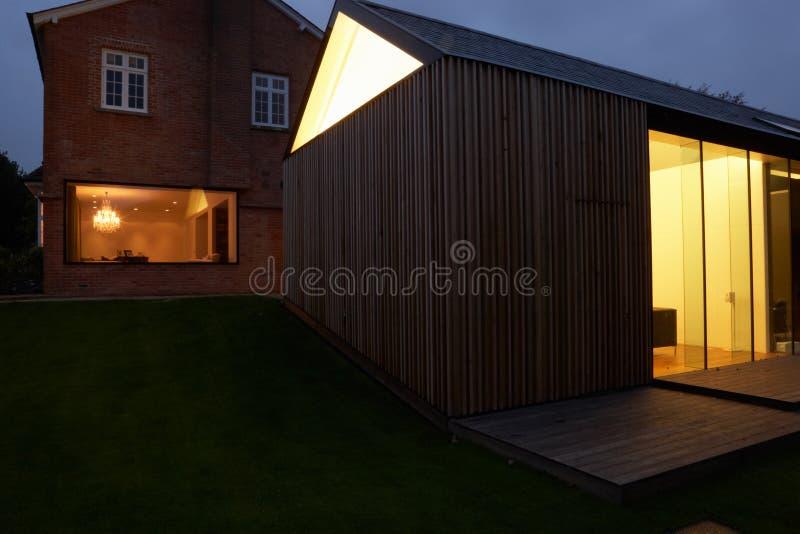 Εξωτερικό του σύγχρονου σπιτιού με την επέκταση τη νύχτα στοκ φωτογραφίες