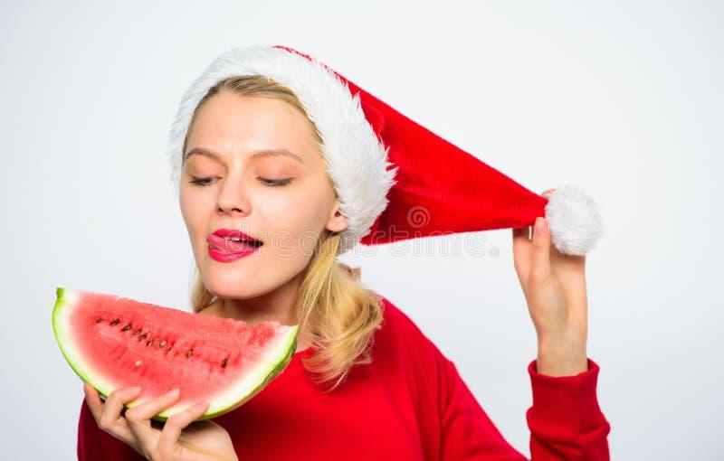 Εξωτικές χειμερινές διακοπές Γιορτάστε το νέο καλοκαίρι έτους Το καπέλο santa ένδυσης κοριτσιών τρώει το άσπρο υπόβαθρο καρπουζιώ στοκ φωτογραφία με δικαίωμα ελεύθερης χρήσης