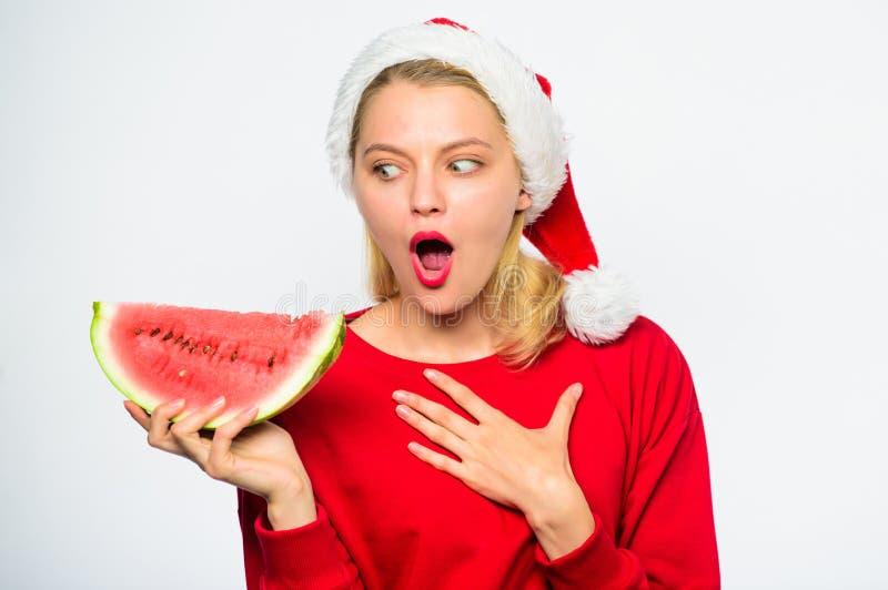 Εξωτικές χειμερινές διακοπές Γιορτάστε το νέο καλοκαίρι έτους Το κορίτσι Χριστουγέννων τρώει το καρπούζι Το καπέλο santa ένδυσης  στοκ φωτογραφία με δικαίωμα ελεύθερης χρήσης