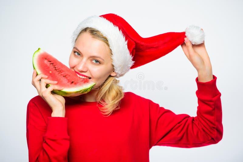 Εξωτική έννοια Χριστουγέννων Το κορίτσι Χριστουγέννων τρώει το καρπούζι Εξωτικές χειμερινές διακοπές Γιορτάστε το νέο καλοκαίρι έ στοκ φωτογραφίες