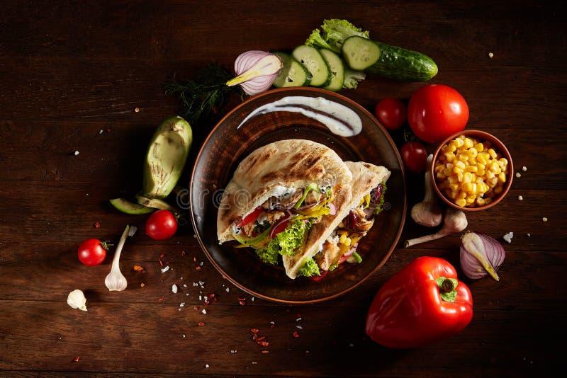 Εξωτικός ακόμα slife με το γεμισμένα pita και τα φρέσκα λαχανικά πέρα από το ξύλινο υπόβαθρο, εκλεκτική εστίαση στοκ φωτογραφία με δικαίωμα ελεύθερης χρήσης