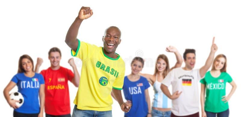 Εορτασμός στόχου ενός βραζιλιάνου ανεμιστήρα ποδοσφαίρου με τους ανεμιστήρες από άλλες χώρες στοκ φωτογραφίες με δικαίωμα ελεύθερης χρήσης