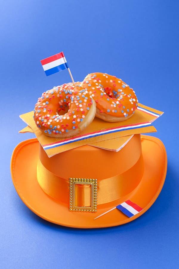 Εορτασμός της ημέρας βασιλιάδων ` s στις Κάτω Χώρες Διακοπές διασκέδασης Πορτοκαλιά γλυκά donuts και ένα καπέλο σε ένα μπλε υπόβα στοκ φωτογραφία με δικαίωμα ελεύθερης χρήσης
