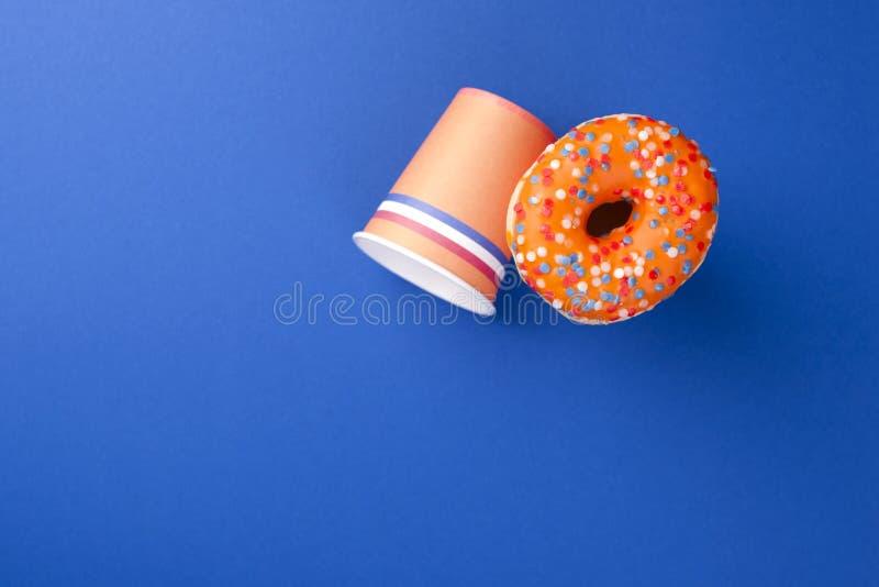 Εορτασμός της ημέρας βασιλιάδων ` s στις Κάτω Χώρες Διακοπές διασκέδασης Πορτοκαλιά φλυτζάνια και γλυκά donuts σε ένα μπλε υπόβαθ στοκ εικόνες με δικαίωμα ελεύθερης χρήσης