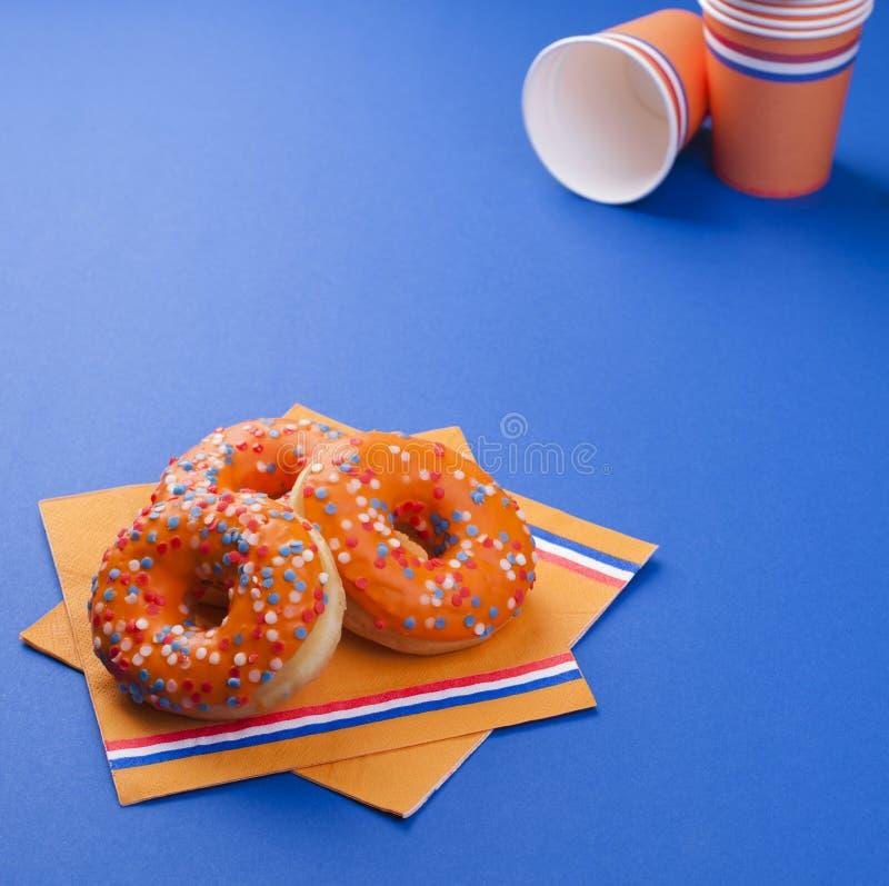 Εορτασμός της ημέρας βασιλιάδων ` s στις Κάτω Χώρες Διακοπές διασκέδασης Πορτοκαλιά εξαρτήματα και γλυκά σε ένα μπλε υπόβαθρο Ελε στοκ φωτογραφίες