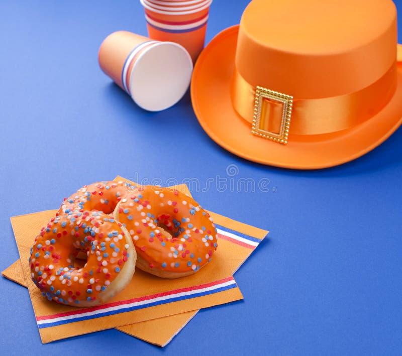 Εορτασμός της ημέρας βασιλιάδων ` s στις Κάτω Χώρες Διακοπές διασκέδασης Πορτοκαλιά εξαρτήματα και γλυκά σε ένα μπλε υπόβαθρο κεί στοκ φωτογραφίες