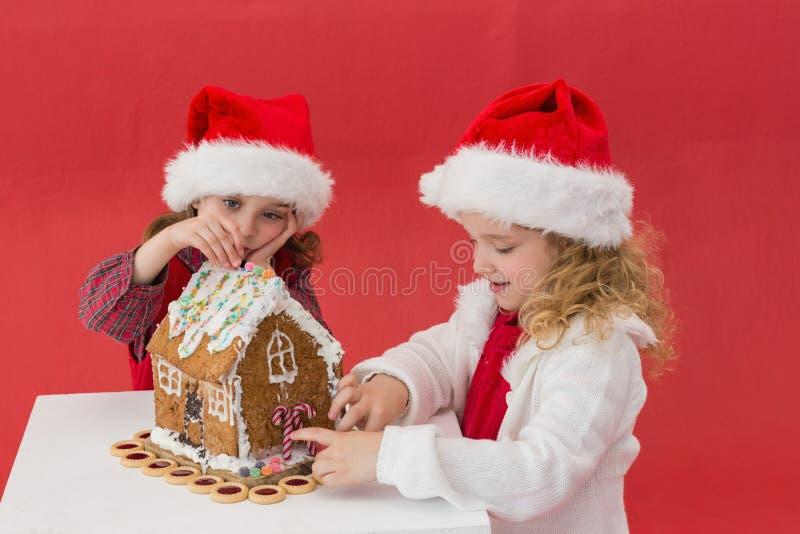 Εορταστικά μικρά κορίτσια που κάνουν ένα σπίτι μελοψωμάτων στοκ φωτογραφία με δικαίωμα ελεύθερης χρήσης