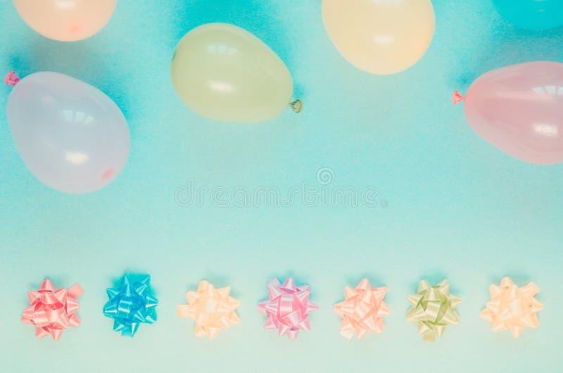 Εορταστικά μπαλόνια και τόξα διακοσμήσεων Colorfu στο μπλε υπόβαθρο στοκ εικόνα