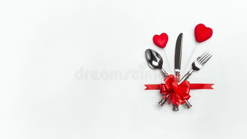 Εορταστική επιτραπέζια θέση που θέτει με το κόκκινο τόξο, μαχαιροπήρουνα και δύο καρδιές στο άσπρο υπόβαθρο, έμβλημα Σχεδιάγραμμα στοκ εικόνα με δικαίωμα ελεύθερης χρήσης