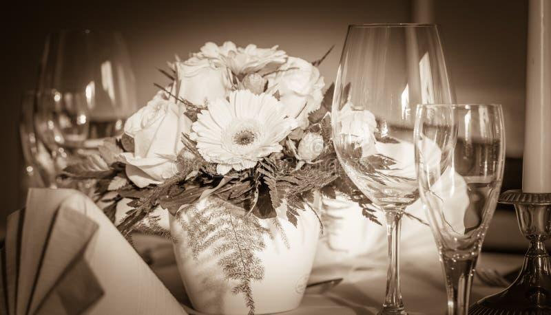 Εορταστική επιτραπέζια ρύθμιση με τα γυαλιά και εξυπηρετημένος και λουλούδια στοκ εικόνες