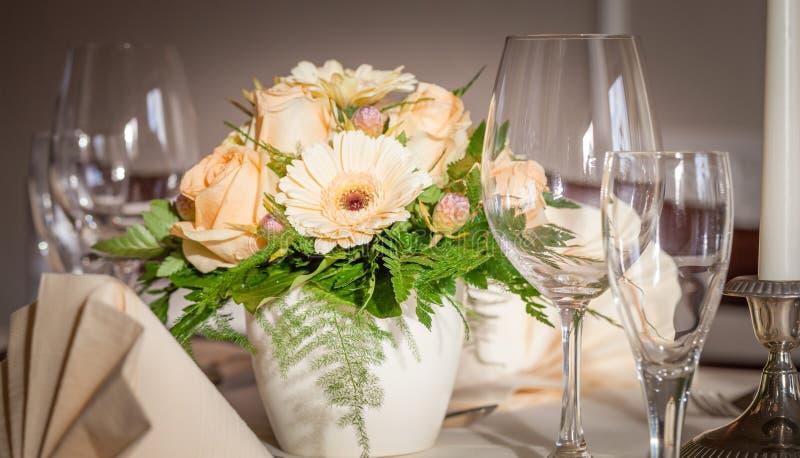 Εορταστική επιτραπέζια ρύθμιση με τα γυαλιά και εξυπηρετημένος και λουλούδια στοκ φωτογραφίες με δικαίωμα ελεύθερης χρήσης