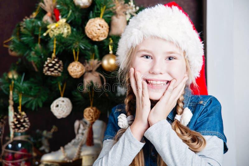 Εορταστική κάμερα χαμόγελου μικρών κοριτσιών ενάντια στο σπίτι με το χριστουγεννιάτικο δέντρο στοκ εικόνες
