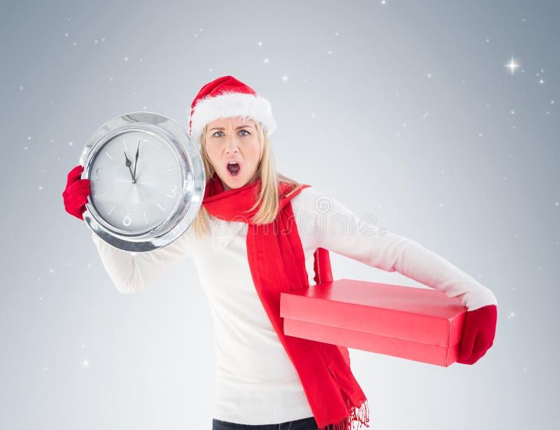 Εορταστική ξανθή εκμετάλλευση ένα ρολόι και ένα δώρο στοκ φωτογραφία