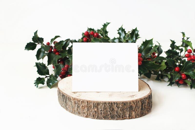 Εορταστική σκηνή προτύπων Χριστουγέννων με τη χειροποίητη κάρτα θέσεων εγγράφου στα ξύλινα κόκκινα μούρα πινάκων και ελαιόπρινου  στοκ φωτογραφίες