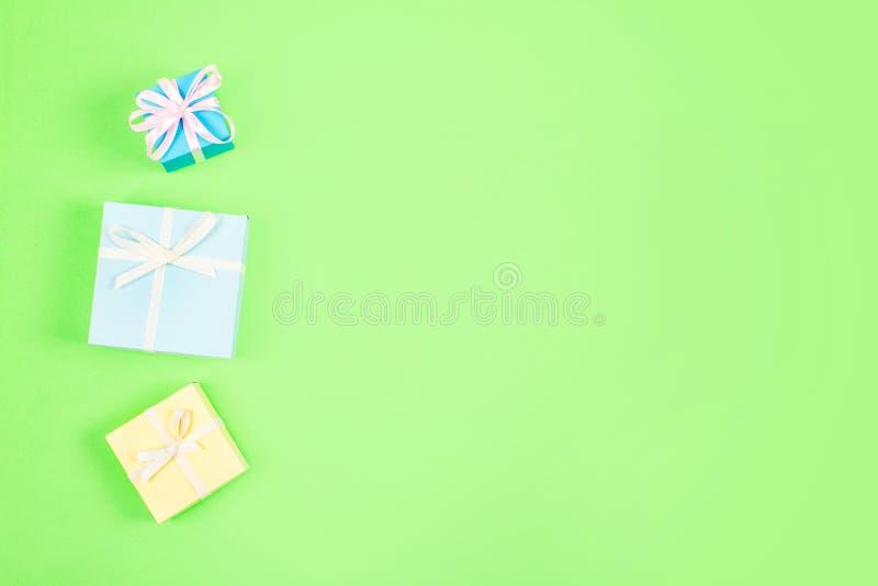 Εορταστικός, γενέθλια, ελάχιστο υπόβαθρο κρητιδογραφιών δώρων Πολύχρωμα κιβώτια δώρων στο πράσινο υπόβαθρο Γάμος, κομψός, αγάπη,  στοκ εικόνα