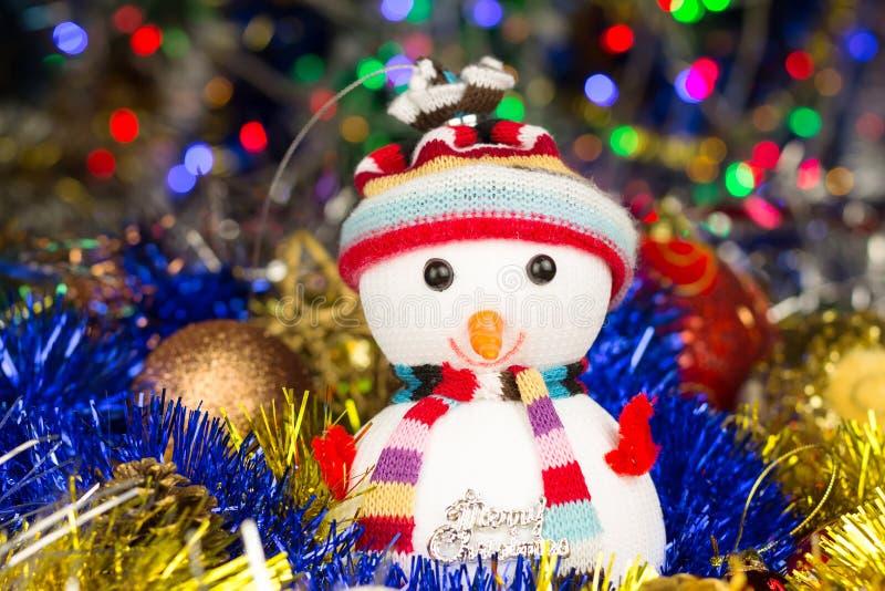 Εορταστικός χιονάνθρωπος με τις σφαίρες Χριστουγέννων, tinsel στο θολωμένο υπόβαθρο φω'των στοκ φωτογραφία