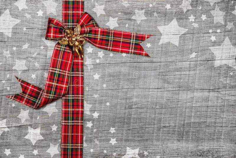 Εορταστικό γκρίζο ξύλινο υπόβαθρο Χριστουγέννων με μια κόκκινη κορδέλλα στοκ εικόνες