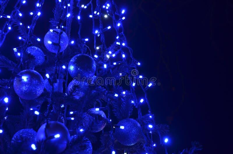 Εορταστικό διακοσμημένο χριστουγεννιάτικο δέντρο με τα μπλε οδηγημένα φω'τα στοκ εικόνες