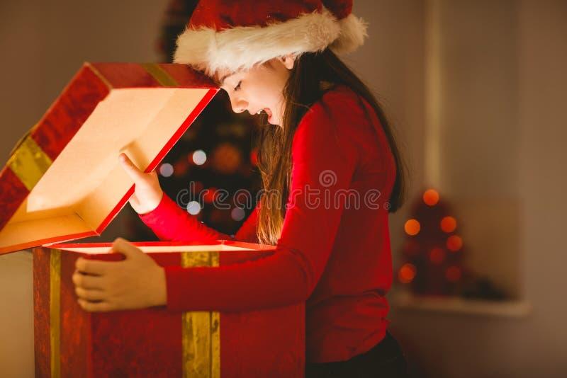 Εορταστικό μικρό κορίτσι που ανοίγει ένα καμμένος δώρο Χριστουγέννων στοκ εικόνα με δικαίωμα ελεύθερης χρήσης
