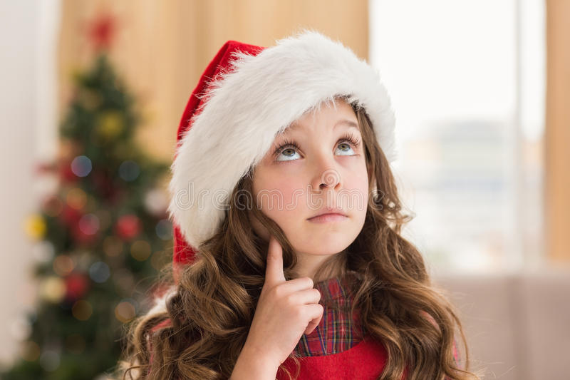 Εορταστικό μικρό κορίτσι που σκέφτεται και που ανατρέχει στοκ φωτογραφίες