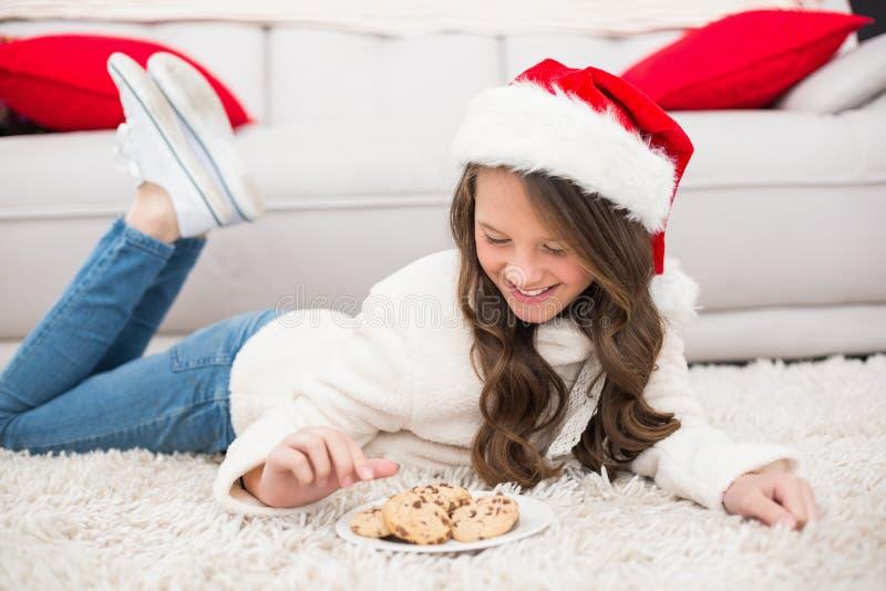 Εορταστικό μικρό κορίτσι που τρώει τα μπισκότα στοκ φωτογραφίες