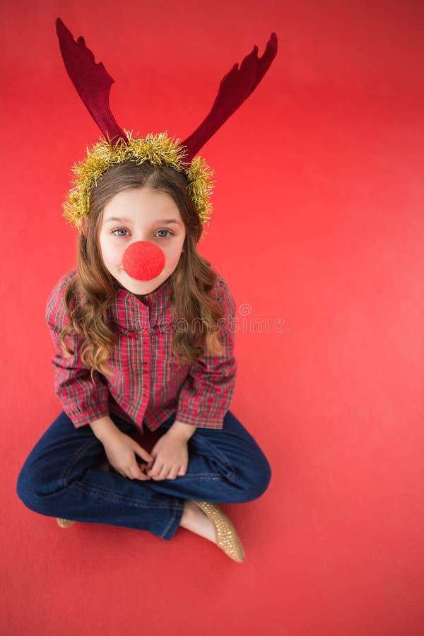 Εορταστικό μικρό κορίτσι που φορά την κόκκινη μύτη στοκ εικόνα
