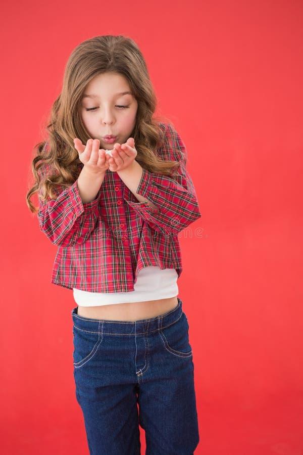 Εορταστικό μικρό κορίτσι που φυσά πέρα από τα χέρια στοκ φωτογραφία