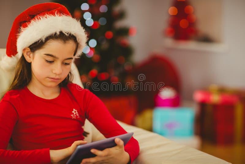 Εορταστικό μικρό κορίτσι που χρησιμοποιεί το PC ταμπλετών στον καναπέ στοκ φωτογραφία