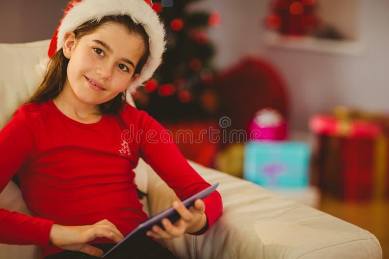 Εορταστικό μικρό κορίτσι που χρησιμοποιεί το PC ταμπλετών στον καναπέ στοκ φωτογραφίες με δικαίωμα ελεύθερης χρήσης