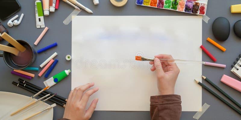 Επάνω όψη της γυναίκας καλλιτέχνιδας που ζωγραφίζει στο έργο της με χρώματα νερού, εργαλεία ζωγραφικής και πινέλο στοκ εικόνα