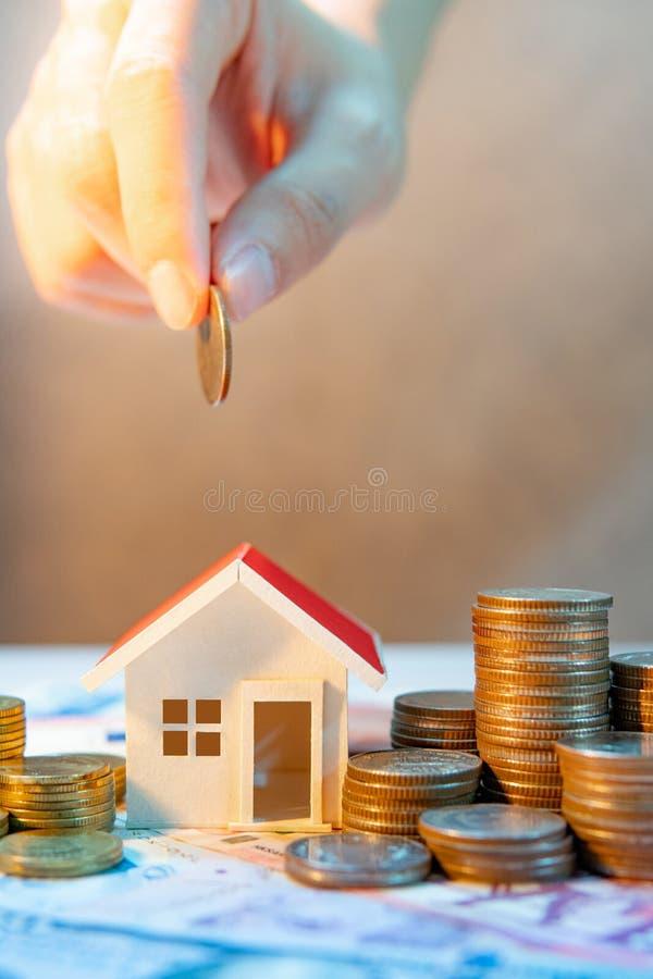 Επένδυση ακίνητων περιουσιών σωρός χρημάτων χεριών έννοιας νομισμάτων που προστατεύει την αποταμίευση στοκ εικόνα με δικαίωμα ελεύθερης χρήσης