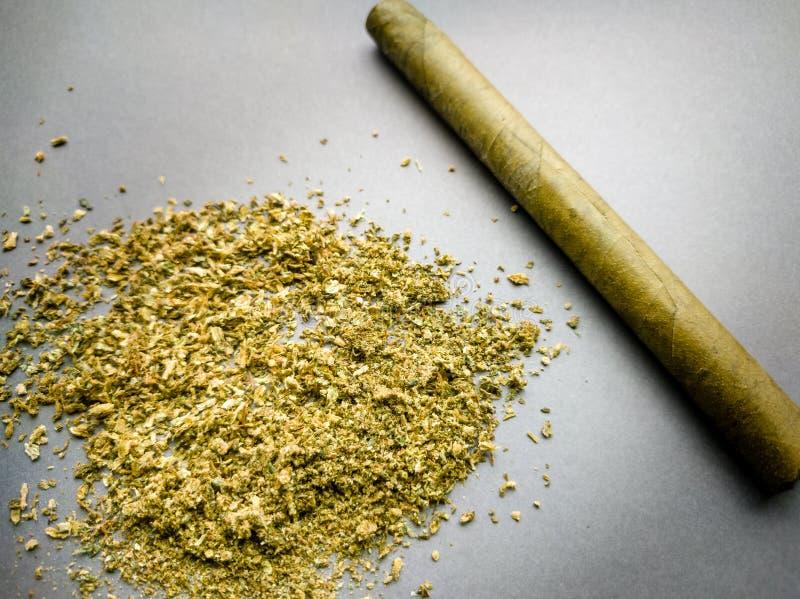 Επίγεια μαριχουάνα και ένα πουράκι σε ένα γκρίζο υπόβαθρο στοκ φωτογραφία