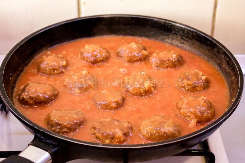 Επίγειο βόειο κρέας Meeatballs στη σάλτσα ντοματών που τηγανίζεται στο τηγάνι από την πλευρά στοκ εικόνα