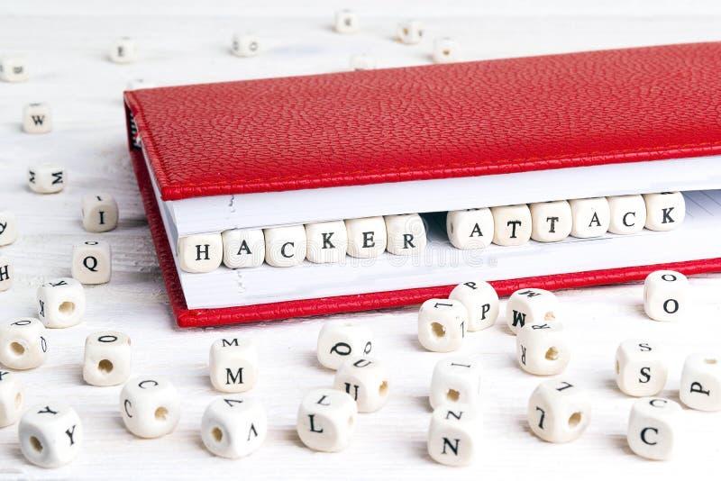 Επίθεση χάκερ φράσης που γράφεται στους ξύλινους φραγμούς στο κόκκινο σημειωματάριο επάνω στοκ φωτογραφία
