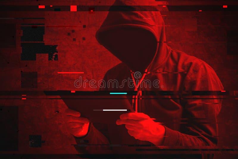 Επίθεση Cyber με τον unrecognizable με κουκούλα χάκερ που χρησιμοποιεί την ταμπλέτα comp
