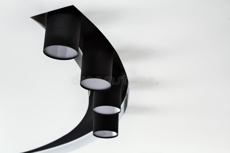 Επίκεντρο ανώτατων λαμπτήρων Μαύρα επίκεντρα στο άσπρο ανώτατο όριο Σύγχρονος φωτισμός για ένα εσωτερικό καθιστικών στοκ φωτογραφίες