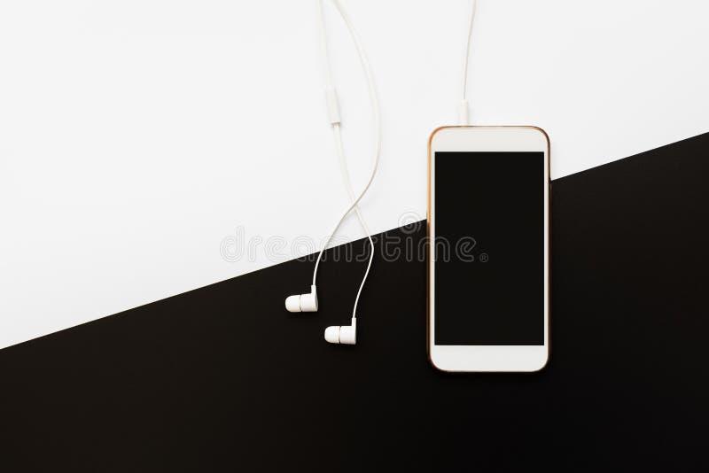 Επίπεδη διάταξη με λευκό smartphone που συνδέεται με λευκά ακουστικά σε λευκό και μαύρο φόντο Κορυφαία προβολή σε προσωπικά αξεσο στοκ φωτογραφία με δικαίωμα ελεύθερης χρήσης