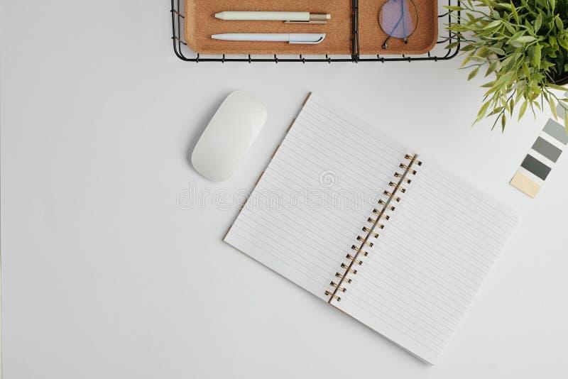 Επίπεδη διάταξη με ποντίκι υπολογιστή, ανοιχτό φορητό υπολογιστή και άλλα αναλώσιμα γραφείου στο γραφείο στοκ εικόνες